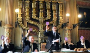 András Heisler (standing) and other Mazsihisz leaders vote in Sunday's assembly