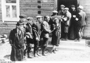 Lithuanian collaborators (with white armbands) arresting Jews in July 1941  Photo By: WIKIMEDIA COMMONS/GERMAN FEDERAL ARCHIVES