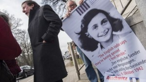 An activist with the Inernational Auschwitz Committee rolls up a poster featuring Holocaust victim Anne Frank outside the regional court of Neubrandenburg during the first day of the trial against former SS medic Hubert Zafke, accused of aiding in 3,681 murders in Auschwitz in 1944, on February 29, 2016. (AFP/John MACDOUGALL)